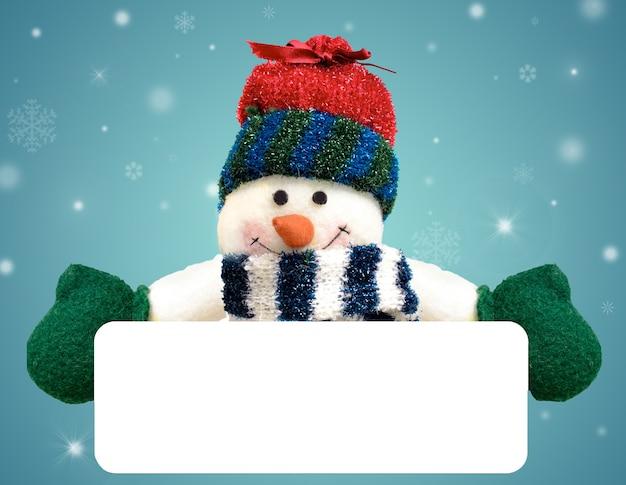 Снеговик держит пустой рождественский баннер на зимнем фоне снега