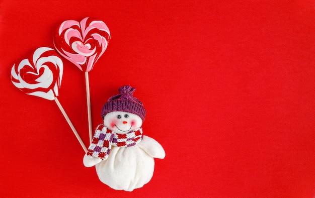 赤い背景にハートの形で伝統的なクリスマスキャンディーを保持している雪だるま