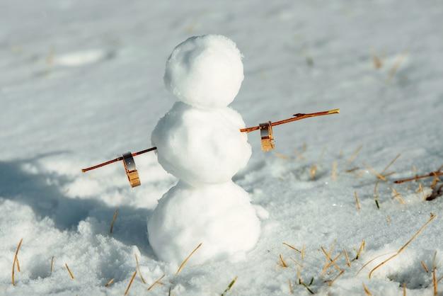 結婚指輪を持っている雪だるま。雪だるまは雪の中に立っています。冬の結婚式のコンセプト