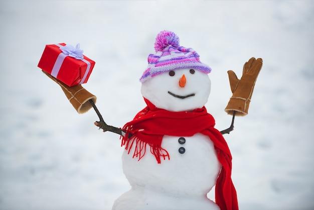 スカーフと帽子の雪だるま。冬のクリスマスの風景に立っているかわいい雪だるま。面白い雪だるま
