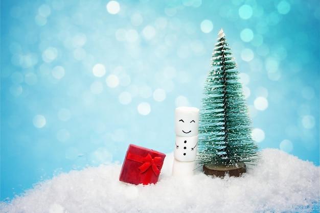 Снеговик стоит возле маленькой ёлки на снегу