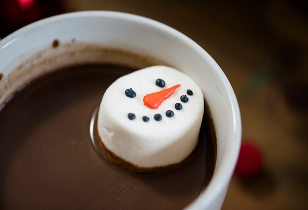 Snowman marshmallow dipped in hot chocolate