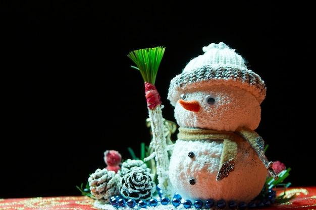 Снеговик на черном фоне. новогодняя игрушка. рождественская открытка