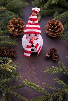 クリスマスツリーとコーンの背景に雪だるま。新年のコンセプト