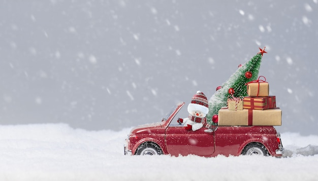 Snowman in red car delivering christmas tree and presents at snowy background.