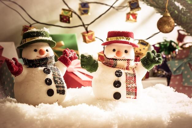 メリークリスマスの電球で静かな夜に雪の山の中に雪だるまを立てる