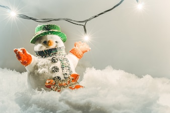 Snowman stand in pile of snow.