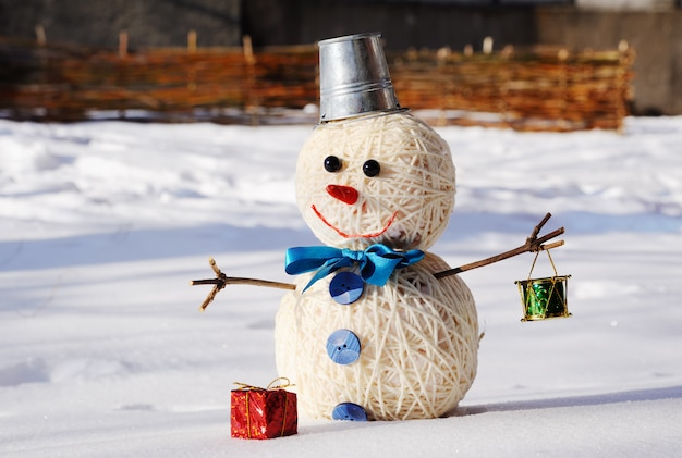 Snowman with a bucket on his head on a background of snow