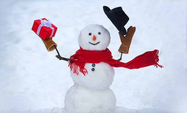 Snowman with gift outdoor. funny snowman in a hat on a snowy meadow on a blurred snow background