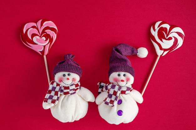Снеговики держат традиционные рождественские конфеты в форме сердца