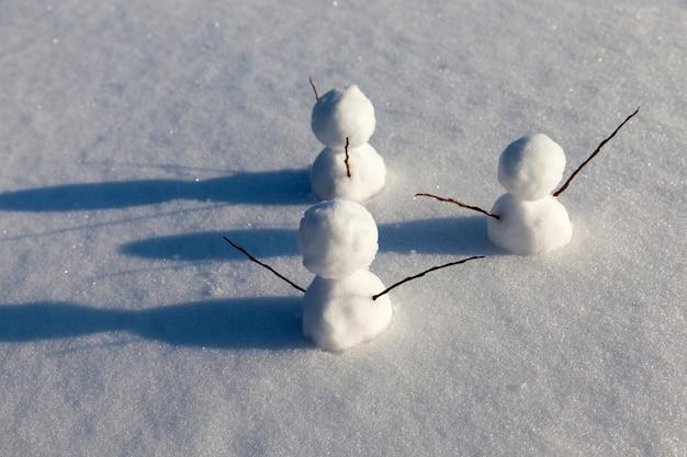 Снеговики из снега зимой, маленькие снеговики стоят на снегу зимой