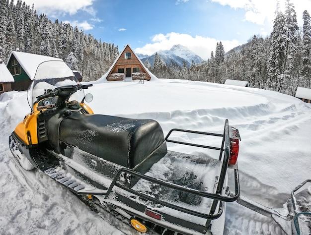 Снегоход в горах и деревянном доме