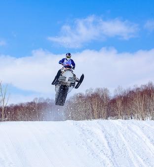 Снегоход в прыжке в высоту над трассой.