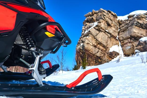 Снегоход на переднем плане на фоне размытого горного зимнего пейзажа