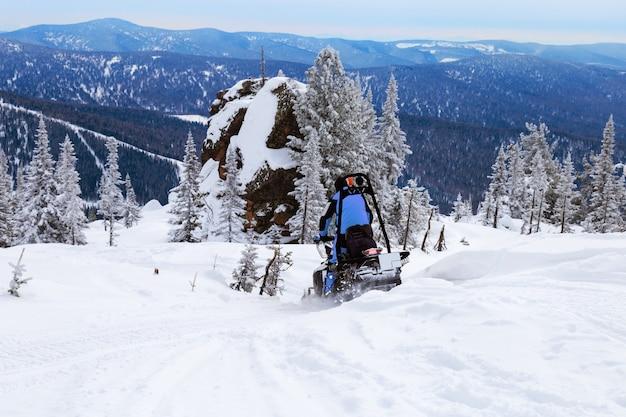 Езда на снегоходе по заснеженной горе