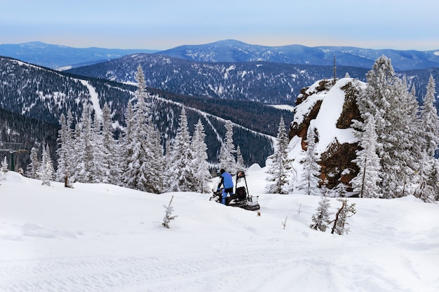 Snowmobile rides on snow-covered mountain.