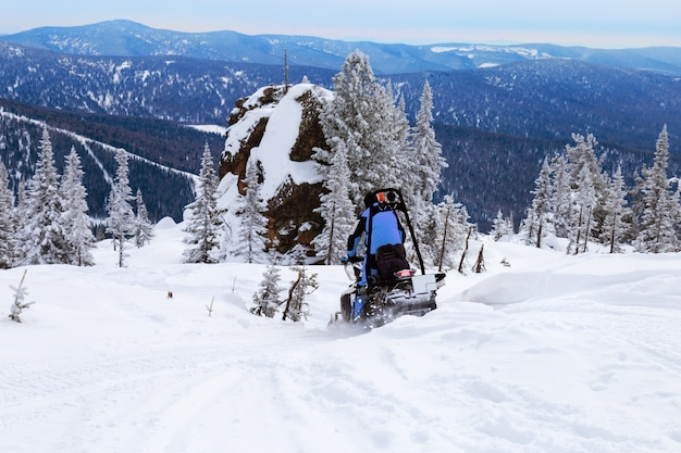 Snowmobile rides on snow covered mountain