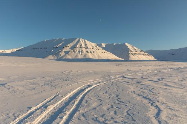Следы снегохода в арктическом зимнем пейзаже со снегом покрыли горы на шпицбергене, норвегия