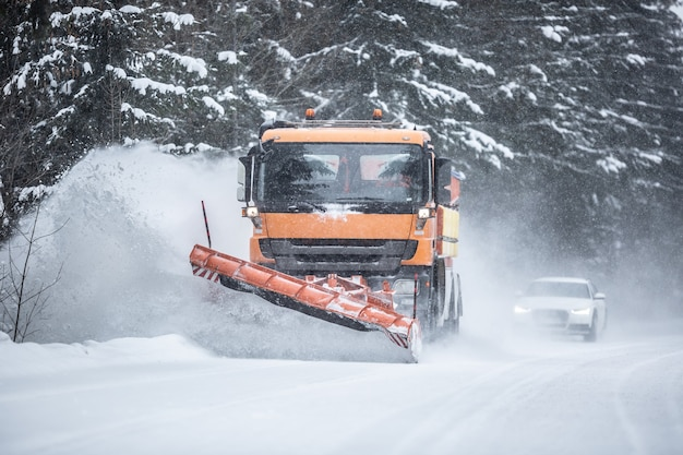 Snowplow clearing road from snow in the forest with traffic lining up behind the truck.