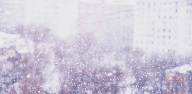 눈보라, 흐릿한 눈송이, 눈 덮인 도시와 나무가 10층에서 보입니다. 톤다운된 크리스마스 분위기.