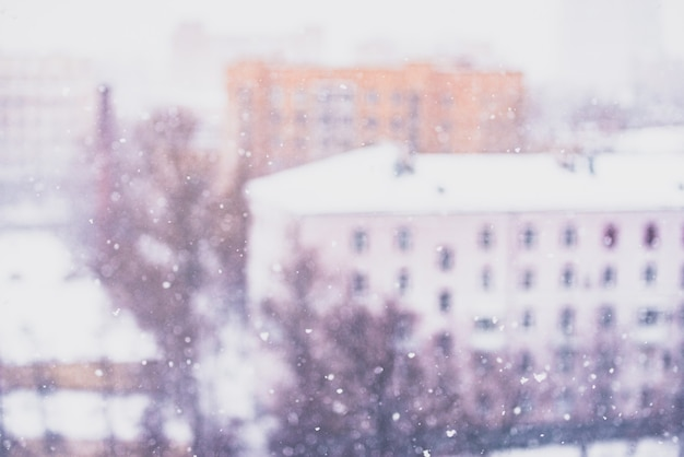 Snowstorm, blurred snowflakes, snow-covered city and trees the view from the 10th floor. toned with christmas mood.