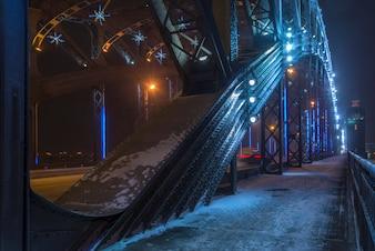 Метель зимой в городе ночью. Большеохтинский мост в Санкт-Петербурге, Россия