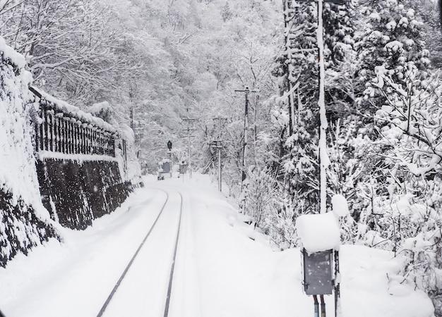 철도 트랙에 눈보라가 있고 시인성이 좋지 않습니다. 일본 도야마시의 겨울.