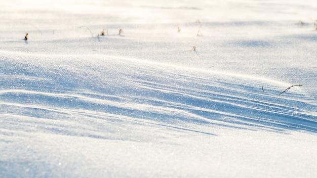 Снежный фон, заснеженная волнистая поверхность земли после метели утром при солнечном свете