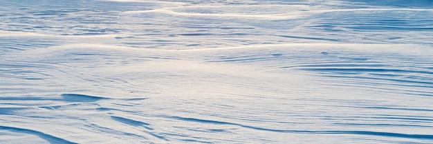눈 덮인 배경, 햇빛에 아침에 눈보라 후 눈 덮인 지구의 물결 모양 표면 프리미엄 사진