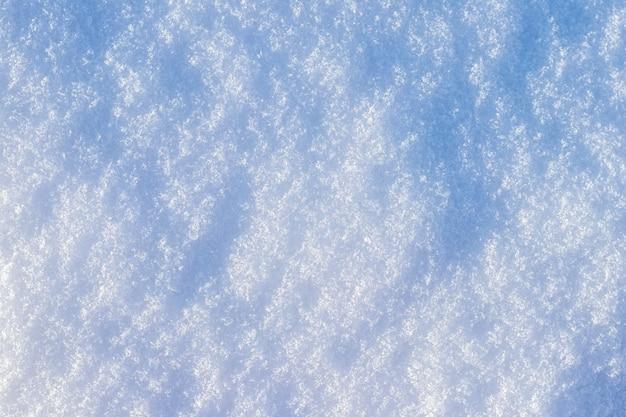 雪の背景、朝日ではっきりと表現された雪の質感を持つ雪の表面