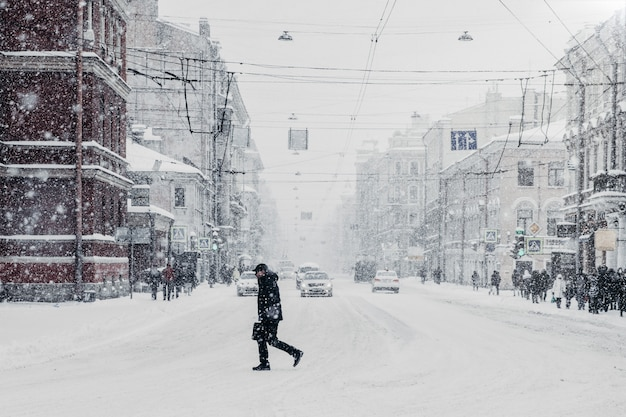 Snowy beautiful busy city with cars and passer by, heavy snowfall. paralysed city during bad winter conditions