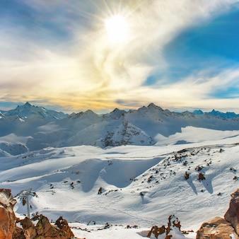 雲の中の雪に覆われた青い山。冬のスキーリゾート
