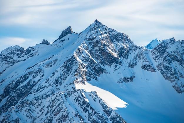 雲の中の雪に覆われた青い山。