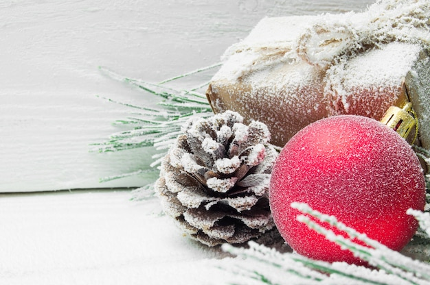 Snowy branch christmas tree and cone and red ball with gift box on white wooden vintage surface