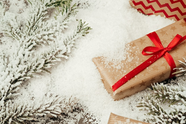 Snowy composition with christmas gift on wooden table