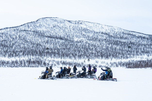 Snowy day with people riding the snowmobiles and a mountain in the distance in the north of sweden