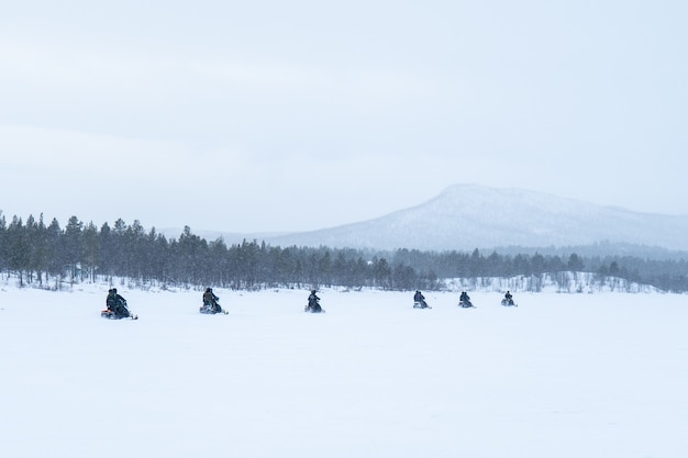 Snowy day with people riding snowmobiles in north of sweden