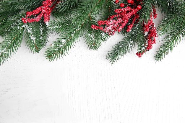 明るい木の表面に雪に覆われたモミの小枝と赤いベリー