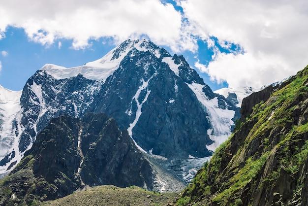 曇った青い空の下の巨大な山腹の後ろに雪に覆われた巨大な山々