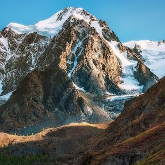 Снежный высокогорный альпийский пейзаж с заснеженной горной вершиной и острыми скалами под голубым небом.