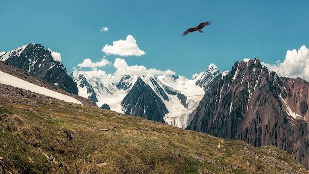 Осенний склон снежной горы. панорамный альпийский пейзаж с заснеженной горной вершиной и острыми скалами под голубым небом. красочный солнечный горный пейзаж со снежной вершиной горы.