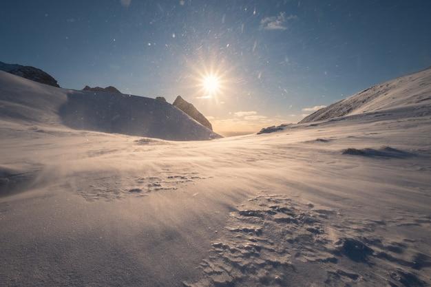 Snowy mountain in blizzard on peak at sunset