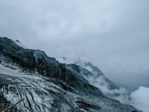 Snowy mountain under cloudy sky