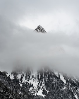 Snowy mountain behind layer of clouds