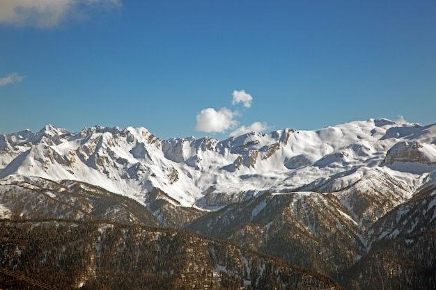 Снежные горные вершины на фоне голубого неба