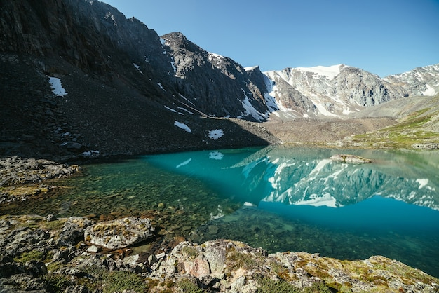 Snowy mountain reflected in clear water of glacial lake. beautiful sunny landscape with glacier reflection in water surface of mountain lake under clear sky. snow on rock reflected in mountain lake.