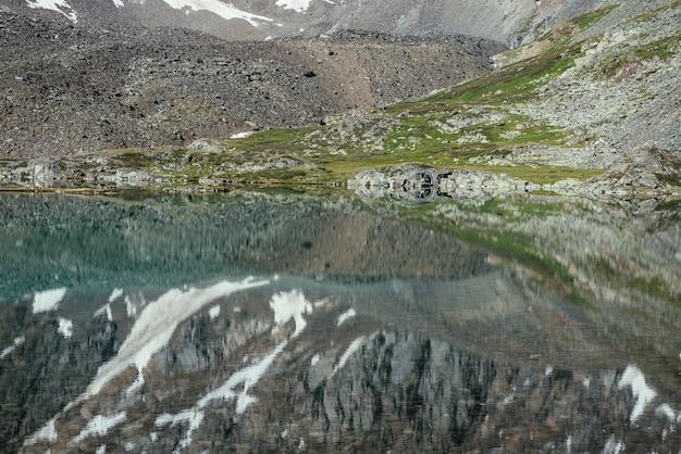 氷河湖の澄んだ水に映る雪山。山の湖の水面に真っ白な氷河が反射する美しい日当たりの良い風景。山の湖に映る岩の上の白い雪。