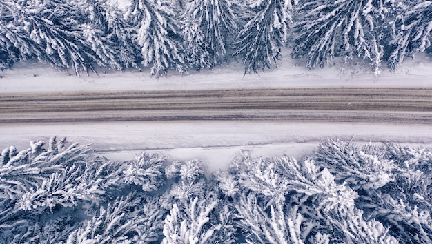 Snowy mountain road and forest, drone view. snowy mountain road and forest, drone view. wonderful winter landscape.