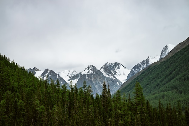 Snowy mountain top between big mountains under overcast sky.