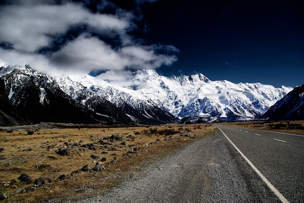 Snowy mountains among clouds from road